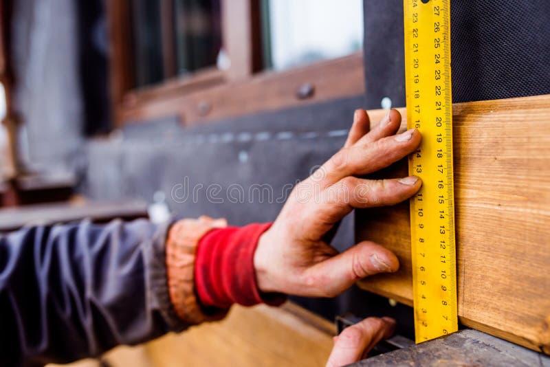 Mano del trabajador irreconocible, haciendo la fachada, BO de madera de medición fotografía de archivo libre de regalías