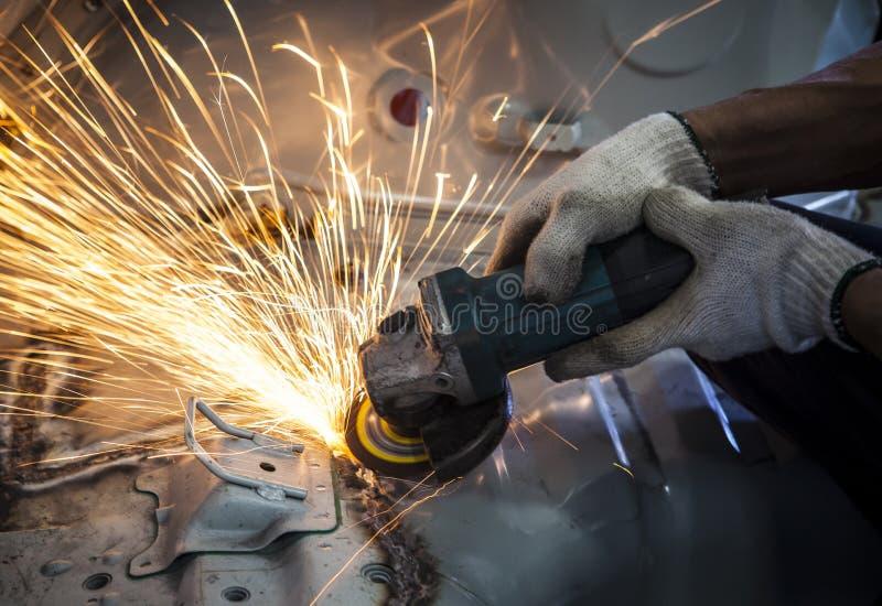 Mano del trabajador que trabaja por la herramienta de la industria que corta el acero con la fractura fi imagenes de archivo