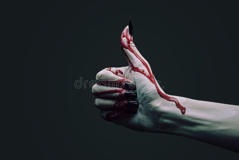 Mano del vampiro con il pollice sul gesto fotografie stock