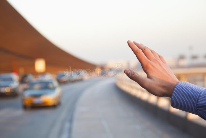 Mano del viaggiatore che ferma un taxi fuori dell'aeroporto immagine stock libera da diritti