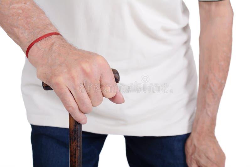 Mano del viejo hombre que sostiene el bastón imagen de archivo