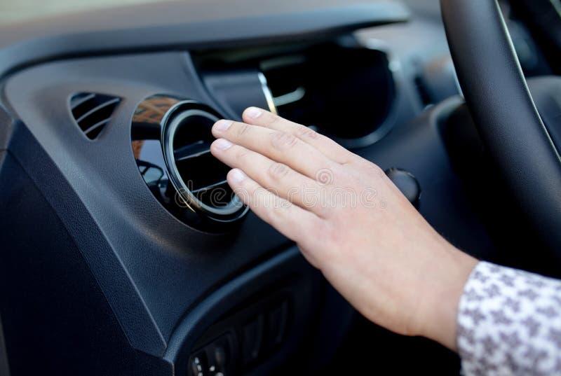 Mano dell'autista sulla griglia di ventilazione dell'aria con il regolatore di potere, dettaglio interno dell'automobile moderna fotografia stock