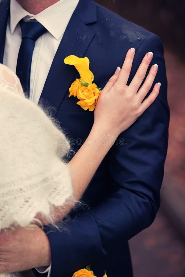 Mano dell'occhiello dello sposo e della sposa fotografia stock
