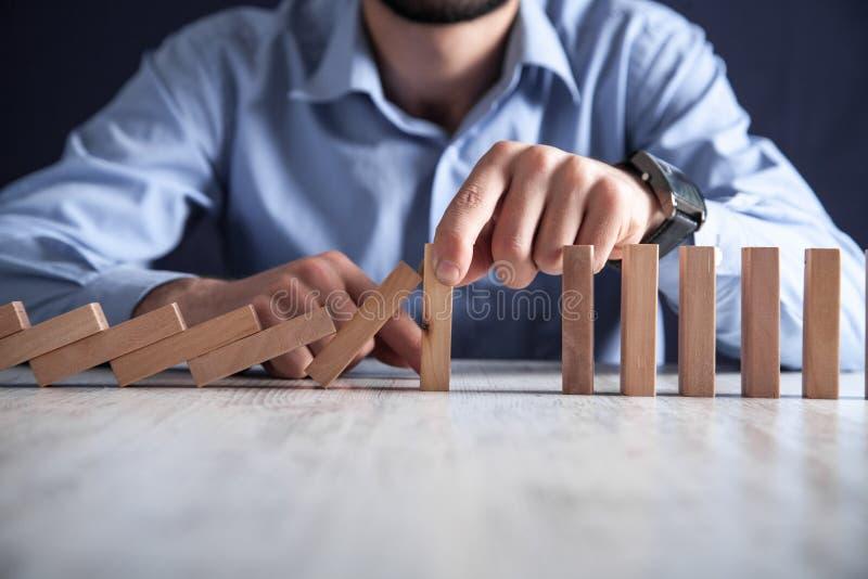 Mano dell'uomo che ferma i blocchi di legno di caduta Rischio, gestione, soluzione immagini stock