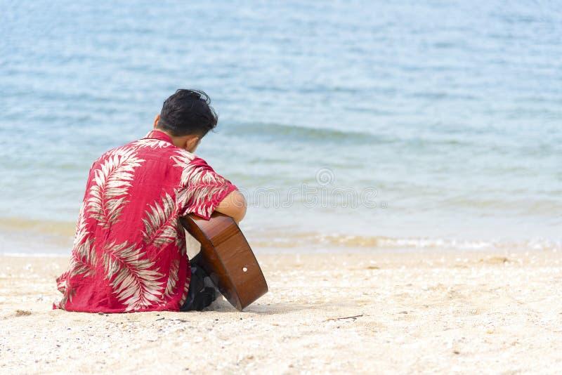 Mano dell'uomo che gioca chitarra sulla spiaggia Musicista acustico che gioca chitarra classica Concetto musicale immagine stock