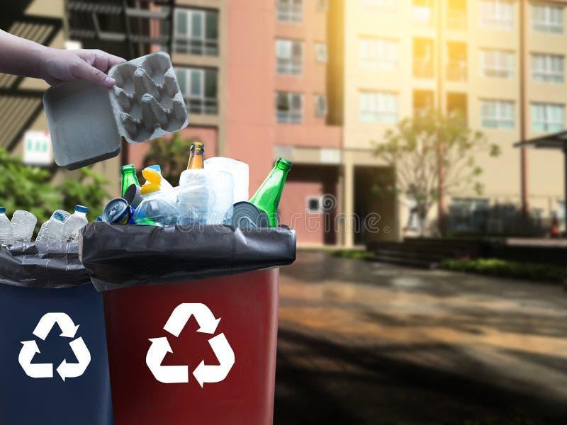 mano dell'uomo che mette riutilizzazione di plastica per il riciclaggio dell'ambiente di concetto immagini stock