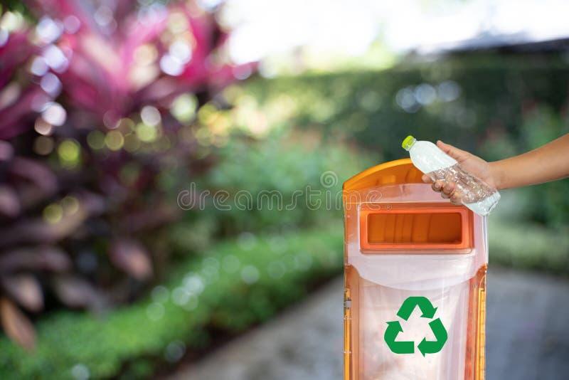 mano dell'uomo che mette riutilizzazione di plastica per il riciclaggio dell'ambiente di concetto fotografia stock