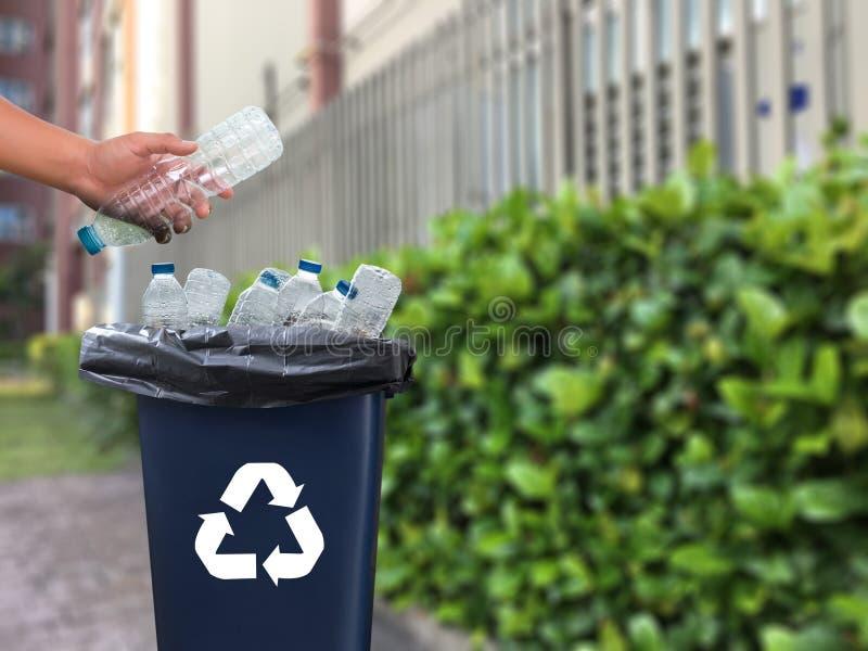 mano dell'uomo che mette riutilizzazione di plastica per il riciclaggio dei environmen di concetto fotografie stock