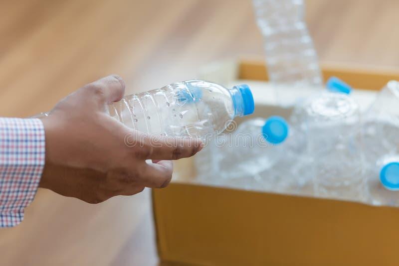 mano dell'uomo che mette riutilizzazione di plastica per il riciclaggio dei environmen di concetto immagini stock