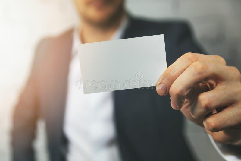 Mano dell'uomo che mostra biglietto da visita in bianco nella parte anteriore fotografia stock