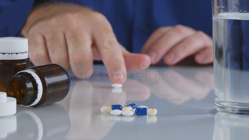 Mano dell'uomo che prende le pillole dalla Tabella per un trattamento medico immagine stock