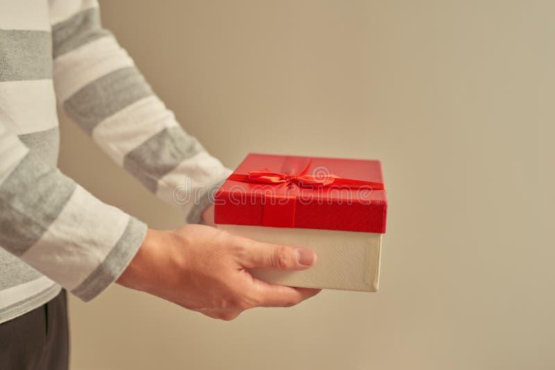 Mano dell'uomo che tiene il contenitore di regalo rosso, regalo dante maschio fotografie stock libere da diritti