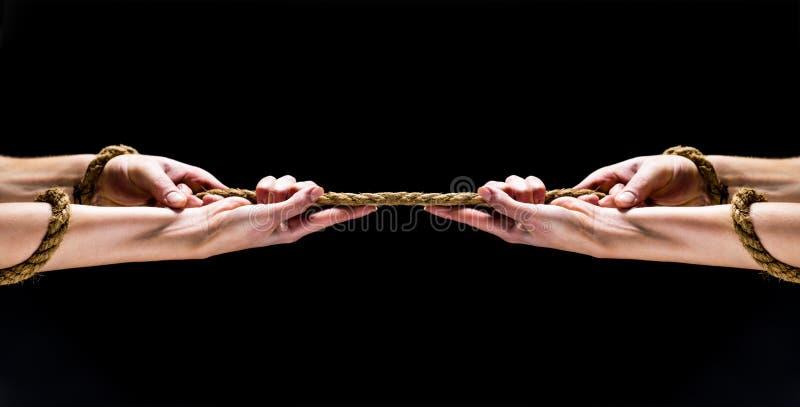 Mano dell'uomo che tiene sopra alla corda Mano tenendo le corde Conflitto, conflitto, corda Salvataggio, gesto d'aiuto o mani Due immagine stock