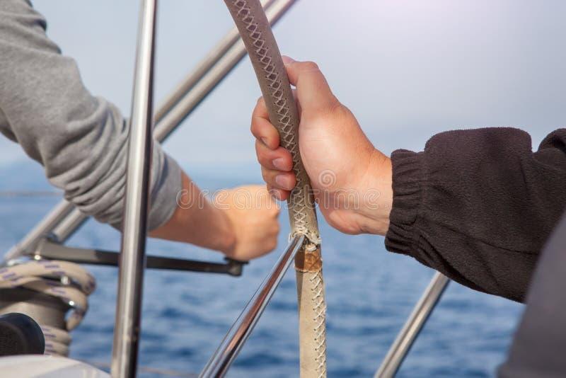 Mano dell'uomo che tiene una ruota dell'imbarcazione a vela fotografie stock