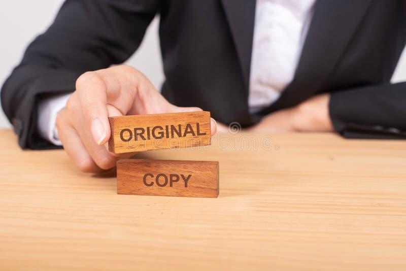 Mano dell'uomo d'affari che sceglie blog di legno con l'origine di parola e dell'icona fotografia stock