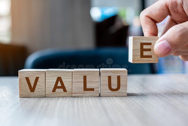 Mano dell'uomo d'affari che tiene il blocchetto di legno del cubo con la parola di affari di valore sul fondo della tavola Concet fotografia stock