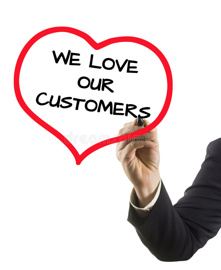 Mano dell'uomo d'affari con il testo di scrittura dell'indicatore amiamo i nostri clienti fotografia stock libera da diritti