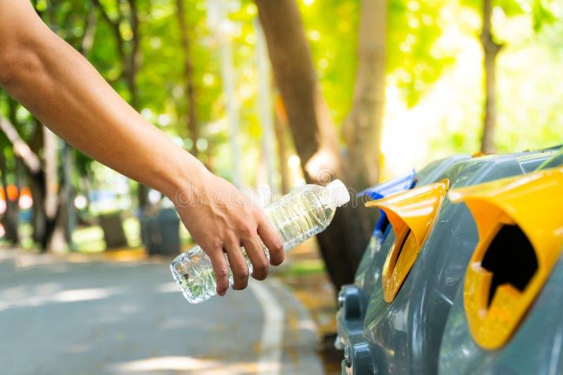 Mano dell'uomo del primo piano che getta bottiglia di acqua di plastica vuota al rec immagini stock