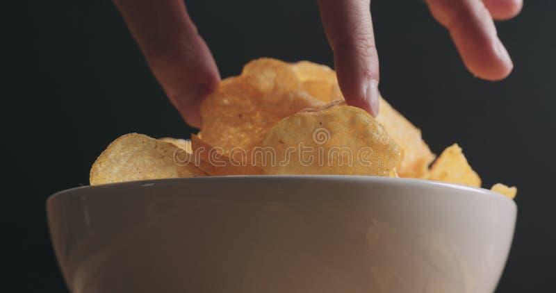 Mano dell'uomo del primo piano che prende la patatina fritta dal colpo bianco di angolo basso della ciotola fotografia stock