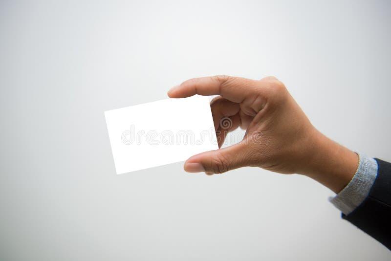 Mano dell'uomo di affari che tiene biglietto da visita in bianco su backgroun bianco fotografia stock