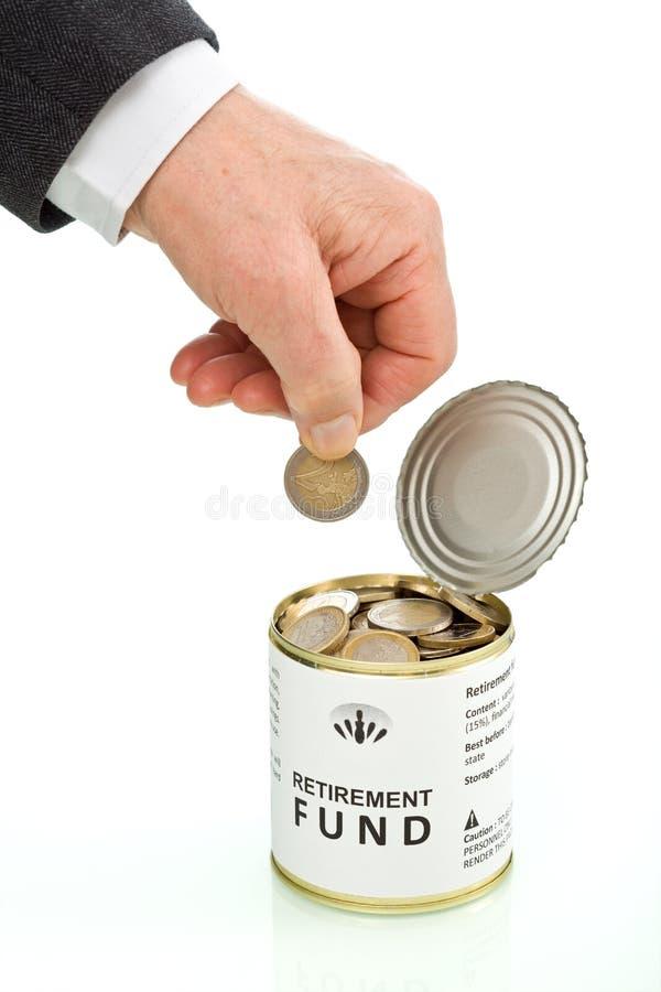 Mano dell'uomo maggiore che mette moneta nel fondo di pensionamento immagine stock