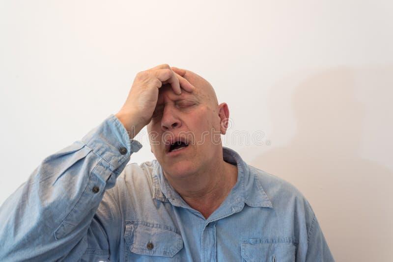 Mano dell'uomo più anziano alla fronte nell'emergenza o nel dolore, calvo, alopecia, chemioterapia, cancro fotografia stock