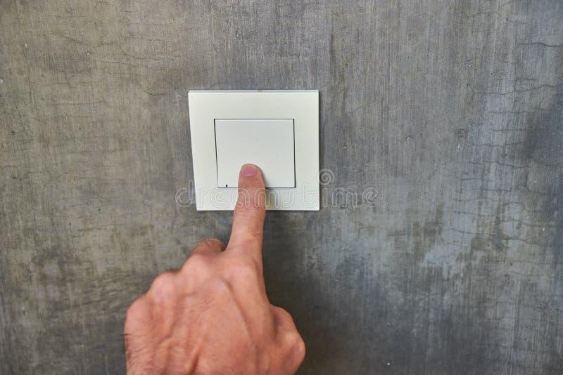Mano dell'uomo, spegnere la luce, commutatore, vista frontale fotografia stock