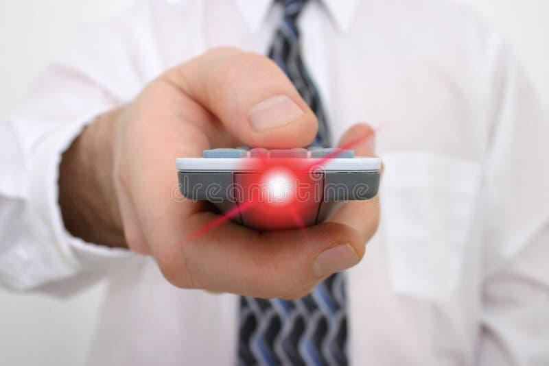 Mano dell'uomo su un telecomando con indicatore luminoso che irradia dal periferico fotografie stock