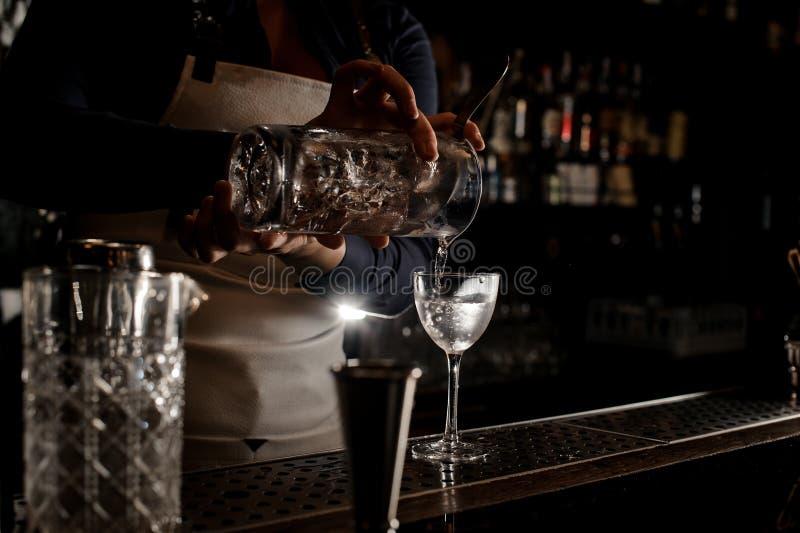 Mano della cameriera al banco che versa cocktail fresco in un vetro fotografia stock libera da diritti