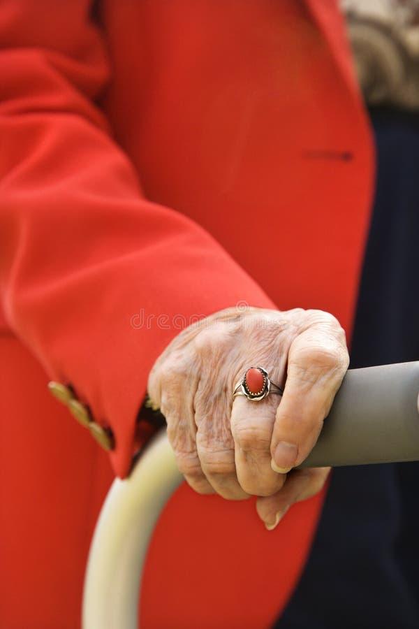 Mano della donna anziana sul camminatore. fotografia stock