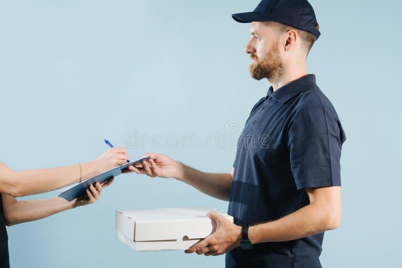 Mano della donna che accetta una consegna da un corriere, forma di carta di firma della scatola con la penna fotografia stock libera da diritti