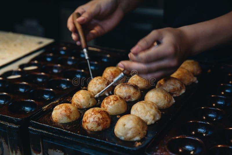 Mano della donna che fa Takoyaki, alimento giapponese della via fotografia stock