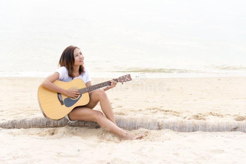 Mano della donna che gioca chitarra sulla spiaggia Musicista acustico che gioca chitarra classica Concetto musicale fotografia stock libera da diritti