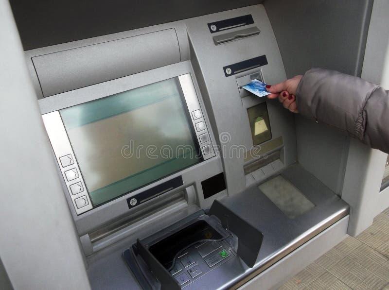 Mano della donna che inserisce la carta di BANCOMAT nella macchina della banca per ritirare soldi fotografie stock