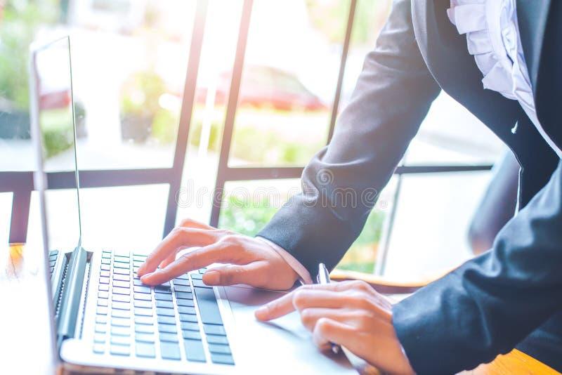 Mano della donna che lavora al computer portatile nell'ufficio immagini stock libere da diritti