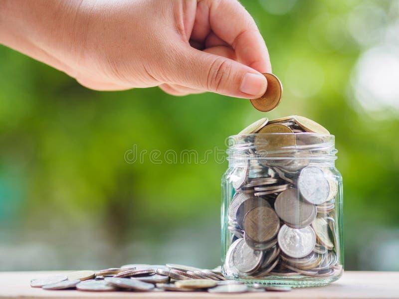 Mano della donna che mette la moneta dei soldi nel barattolo di vetro per soldi di risparmio S fotografie stock libere da diritti