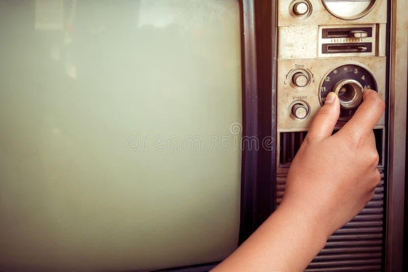 Mano della donna che regola televisione d'annata con il bottone di controllo fotografia stock libera da diritti
