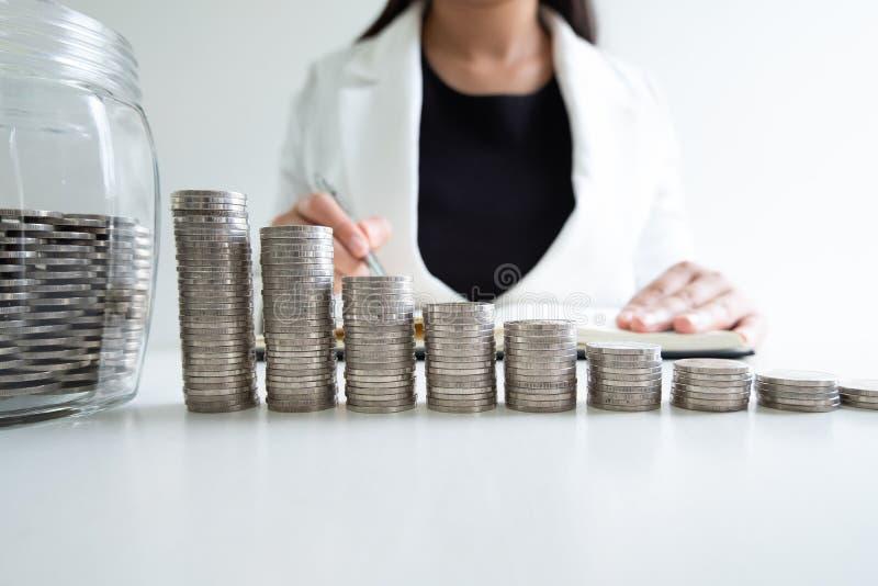 Mano della donna che scrive le monete nella banca della bottiglia di vetro con l'istogramma delle monete fotografia stock libera da diritti