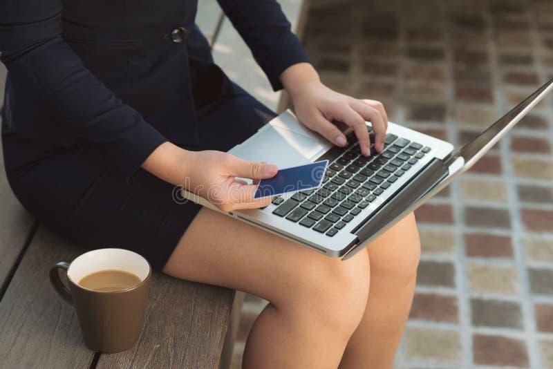 Mano della donna che tiene fine della carta di credito e del computer portatile sull'esterno fotografia stock libera da diritti