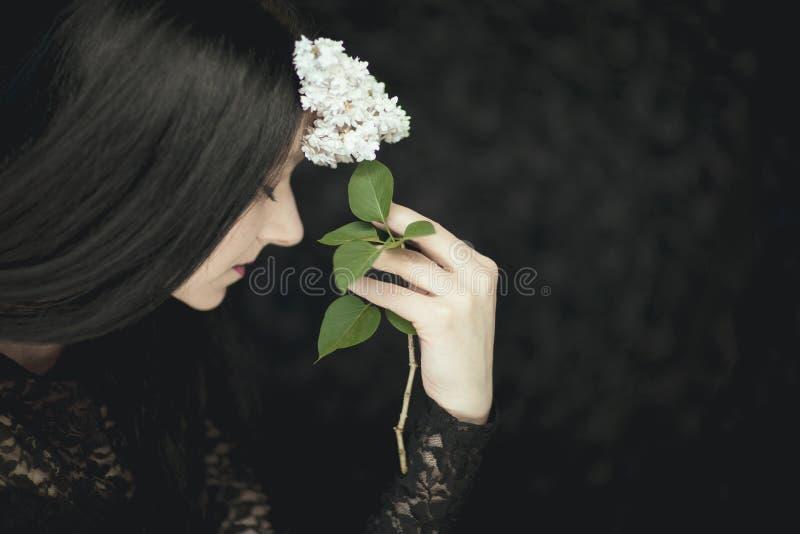 Mano della donna che tiene i fiori lilla bianchi freschi al suo fronte, colpo rurale sensuale atmosferico molto scuro dello studi fotografie stock