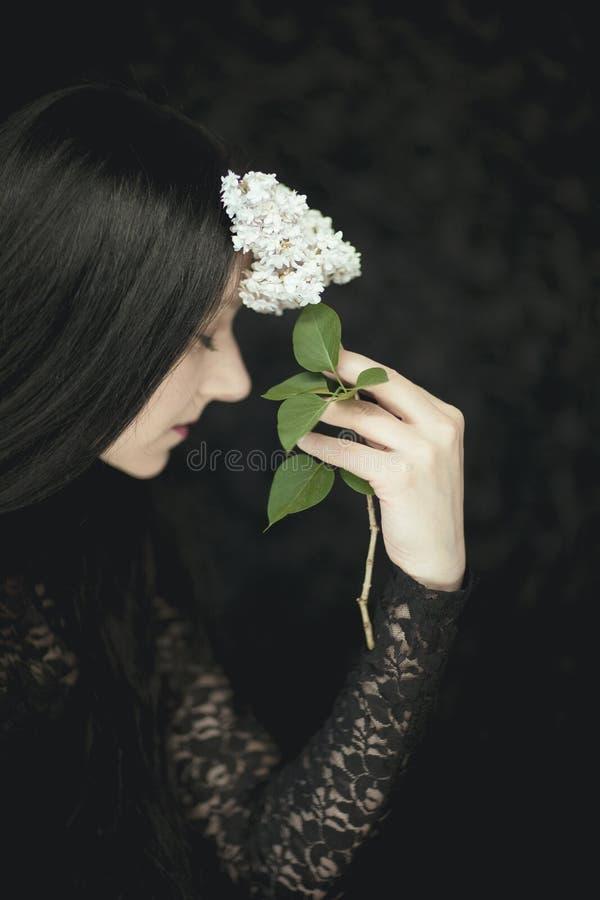 Mano della donna che tiene i fiori lilla bianchi freschi al suo fronte, colpo rurale sensuale atmosferico molto scuro dello studi immagini stock
