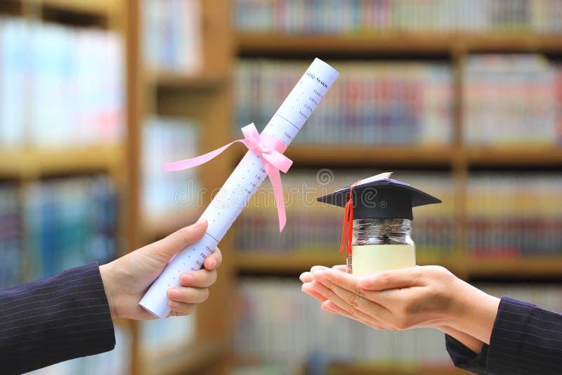 Mano della donna che tiene i soldi delle monete in bottiglia di vetro con i laureati cappello e diploma sullo scaffale per libri  fotografia stock libera da diritti