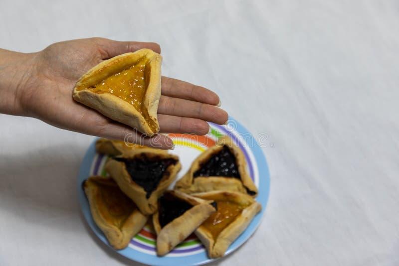 Mano della donna che tiene il biscotto del hamantash sopra il piatto variopinto con pi? biscotti del hamantash fotografia stock
