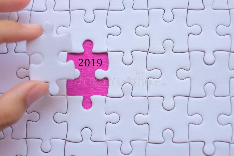Mano della donna che tiene il pezzo bianco del puzzle con le parole 2019 Risoluzioni di affari, successo, scopi, nuovo inizio del fotografia stock