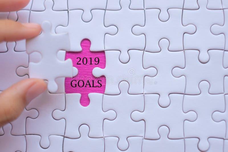 Mano della donna che tiene il pezzo bianco del puzzle con le parole 2019 SCOPI Risoluzioni di affari, successo, scopi, nuovo iniz immagini stock