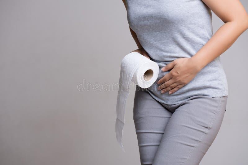 Mano della donna che tiene il suo addome della biforcazione e tessuto o rotolo più basso della carta igienica Disordine, diarrea, fotografie stock