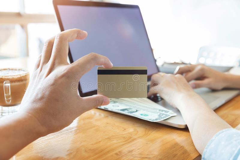 Mano della donna che tiene la carta di credito e che per mezzo del computer portatile per cercare sito Web acquisto online immagine stock