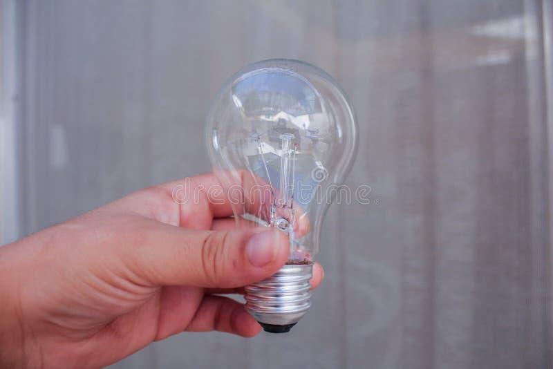 Mano della donna che tiene lampadina fotografia stock