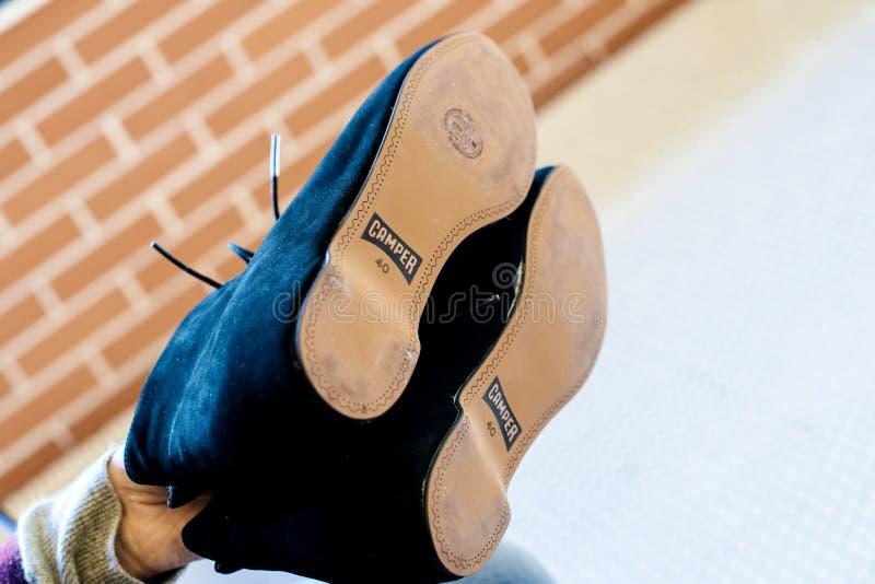 Mano della donna che tiene le paia di nuove scarpe del campeggiatore fotografia stock libera da diritti