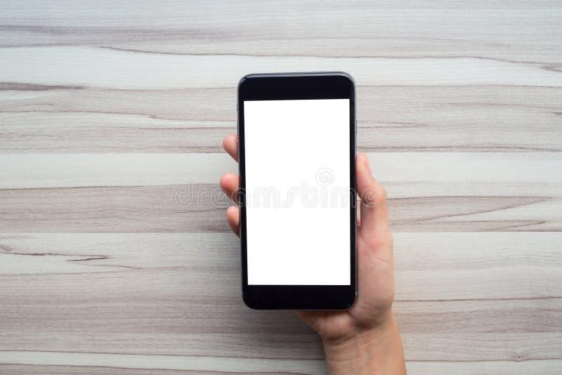 Mano della donna che tiene lo smartphone nero immagini stock